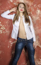Young beautiful long haired brown haired woman in unbuttoned white shirt and jeans a sitting on a chair Stock Image