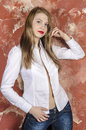 Young beautiful long haired brown haired woman in unbuttoned white shirt and jeans a sitting on a chair Royalty Free Stock Photo