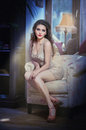 Young beautiful luxurious woman sitting on a vintage couch in classic interior seductive Royalty Free Stock Photography