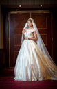 Young beautiful luxurious woman in wedding dress posing in luxurious interior. Gorgeous elegant bride with long veil. Full length