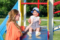 Young beautiful mother and daughter baby girl happy family playing on the swing, and ride in the amusement park smiling Royalty Free Stock Photo
