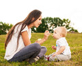 Young beautiful mother feeding her baby puree outdoors in sunlight Royalty Free Stock Photo
