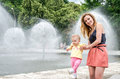 Young beautiful mother with her daughter walking in the park fountain that sprays water Royalty Free Stock Photo