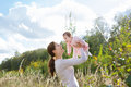 Young beautiful mother holding a baby girl wearing a pink dress in a meadow