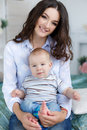 Young beautiful mother holding baby son on her lap, sitting on a bed Royalty Free Stock Photo
