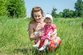 Young beautiful mother playing with her daughter baby in grass outdoors happy family Royalty Free Stock Image