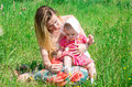 Young beautiful mother playing with her daughter baby in grass outdoors happy family Stock Photography