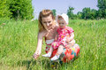Young beautiful mother playing with her daughter baby in grass outdoors happy family Stock Images