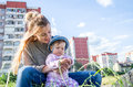 Young beautiful mother playing with her daughter on the playground in the grass sitting on wheels Royalty Free Stock Photos
