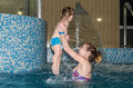 Young beautiful naked mother playing with her daughter smiling in the water in the spa pool - happy family, daughter in diapers, a Royalty Free Stock Photo