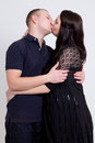 Young beautiful pregnant woman and her husband kissing over grey women background Royalty Free Stock Images