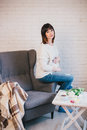 Young beautiful pregnant woman sitting on a grey chair Royalty Free Stock Photo