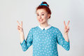 Young beautiful redhead girl with blue dress and head band showing peace sign. Royalty Free Stock Photo