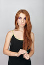 Young beautiful redhead woman with violet eyes makeup posing against gray studio background Royalty Free Stock Photo
