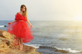 Young beautiful romantic woman at sea shore in red dress Royalty Free Stock Photography
