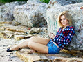 Young beautiful sensual blonde girl outdoors sitting on the rocks Stock Photography