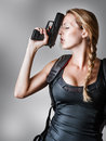 Young beautiful sexy blond woman holding handgun in hand Stock Photo