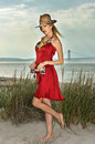 Young beautiful sexy blonde woman wearing straw hat and elegant red dress posing on the beach. Royalty Free Stock Photo