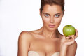 Young beautiful sexy girl with dark hair, bare shoulders and neck, holding big green apple to enjoy the taste and are dieting, hea Royalty Free Stock Photo