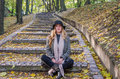 Young beautiful sexy girl model posing in the autumn park among fallen yellow leaves on the old stairs in a hat, coat, jeans and b Royalty Free Stock Photo