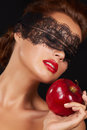 Young beautiful sexy woman with dark lace on eyes bare shoulders and neck holding big red apple to enjoy the taste and are dietin Stock Photo