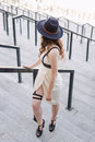 Young beautiful sexy woman wearing trendy outfit, white dress, black hat and leather swordbelt. Longhaired brunette Royalty Free Stock Photo