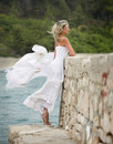 Young beautiful and sexy woman white dress wind blonde stands next to the sea her weaves in the windy weather Stock Images