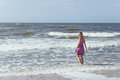 Young beautiful slim girl standing on the beach on a sunny summer day, a strong wind on the sea Royalty Free Stock Photo