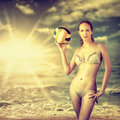 Young beautiful slim volleyball woman holding a at sunset over the sea Stock Photography