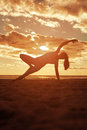 Young beautiful slim woman silhouette practices yoga on the beac Royalty Free Stock Photo