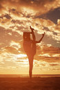 Young beautiful slim woman silhouette practices yoga on the beac beach at sunset at sunrise Royalty Free Stock Image