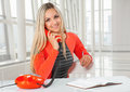 A young beautiful smiling caucasian businesswoman sitting at table speaking with phone and looking at camera Stock Photo