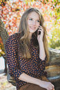 Young beautiful smiling girl talking on mobile phone in park Royalty Free Stock Photo
