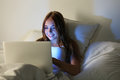 Young beautiful smiling woman lie in bed hold hands on laptop co Royalty Free Stock Photo