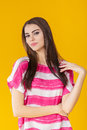 Young beautiful smiling woman with long hair in pink shirt on yellow background. Royalty Free Stock Photo
