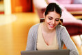 Young beautiful smiling woman looking at laptop home Stock Photos