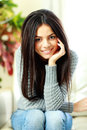 Young beautiful smiling woman sitting on the armchair at home Stock Photos