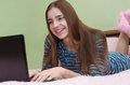 Young beautiful smiling woman using laptop computer lying on bed Royalty Free Stock Photo