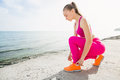 Young beautiful sporty girl in pink uniform on sea. Ties shoelaces Royalty Free Stock Photo