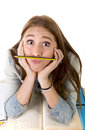 Young beautiful student holding pen between nose and lips as mou Royalty Free Stock Photo