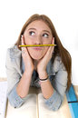 Young beautiful student holding pen between nose and lips as mustache Royalty Free Stock Photo