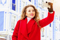 Young, beautiful and stylish blonde hair girl in red coat taking a selfie on her phone. Womens fashion. Royalty Free Stock Photo