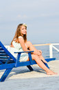 Young beautiful stylish fashion woman sitting on lounger at sea pier happy smiling bright summer day Stock Images