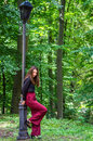 Young beautiful teenager girl with long hair walking in Striysky park in Lviv, posing near a lamp to illuminate the bushes and tre Royalty Free Stock Photo