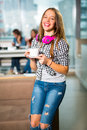 Young beautiful teenager girl sitting in cafe with a white cup, Royalty Free Stock Photo