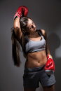 Young beautiful tired woman during fitness and boxing a dark background Stock Photo