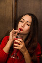 Young and beautiful ukrainian girl is sexy drinking red smoothie cocktail enjoing it she has lips closed eyes she Stock Image