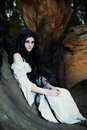Young beautiful witch with long dark hair in root of old tree Royalty Free Stock Photo