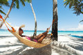 Young beautiful woman on the beach relaxing hammock Royalty Free Stock Images