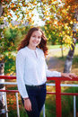 Young beautiful woman. Beauty smiling teenager girl in autumn park Royalty Free Stock Photo